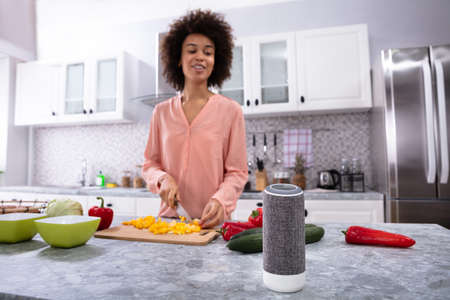 Photo pour Wireless Speaker In Front Of Woman Cutting Vegetables On Chopping Board In The Kitchen - image libre de droit