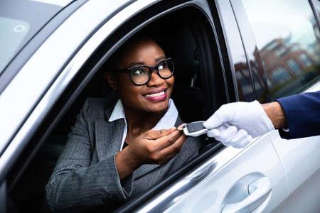 Foto de Close-up Of Happy African Businesswoman Sitting Inside Car Giving Car Key To Valet - Imagen libre de derechos