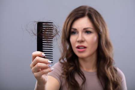 Foto de Close-up Of A Worried Woman Holding Comb Suffering From Hairloss - Imagen libre de derechos