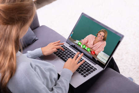Photo pour Close-up Of A Girl Video Conferencing With Happy Female Teacher On Laptop - image libre de droit