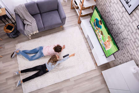 Photo for Mother And Daughter Lying On Carpet Watching Television At Home - Royalty Free Image