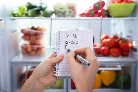 Photo for Hand Making List Of Food On Spiral Notepad In Front Of An Open Refrigerator - Royalty Free Image