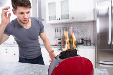 Photo for Portrait Of Scary Man Looking At Slice Of Burn Coming Out Of Toaster - Royalty Free Image