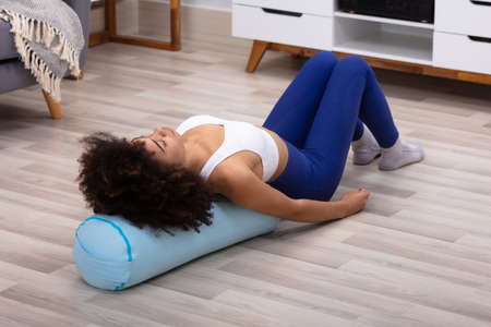 Photo pour Close-up Of A Young African Woman Lying On Pillow Exercising - image libre de droit