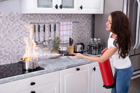 Foto de Woman Using Fire Extinguisher To Stop Fire On Burning Cooking Pot In The Kitchen - Imagen libre de derechos