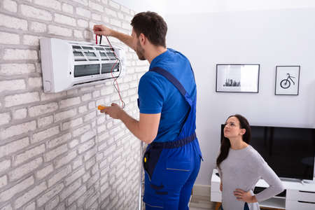 Photo pour Smiling Woman Looking At Male Technician Repairing Air Conditioner With Digital Multimeter At Home - image libre de droit
