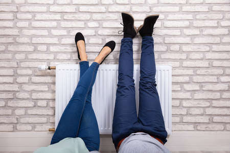 Photo for Close-up Of A Couple Warming Up Their Feet On White Radiator At Home - Royalty Free Image