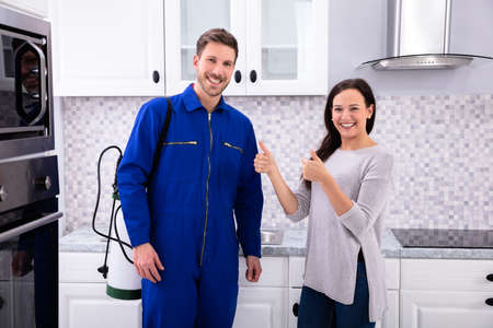 Photo pour Woman Showing Thumbs Up With Pest Control Worker Standing In Kitchen - image libre de droit