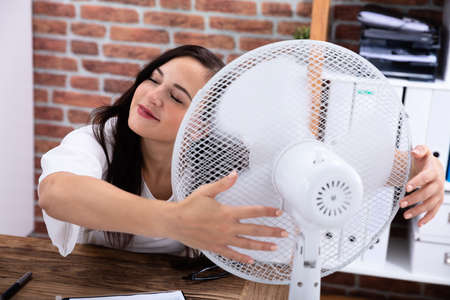 Foto de Smiling Young Woman Enjoying Breeze With Electric Fan At Office - Imagen libre de derechos