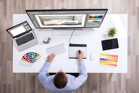 Foto für Elevated View Of Male Graphic Designer Working On Graphic Tablet Over White Desk - Lizenzfreies Bild