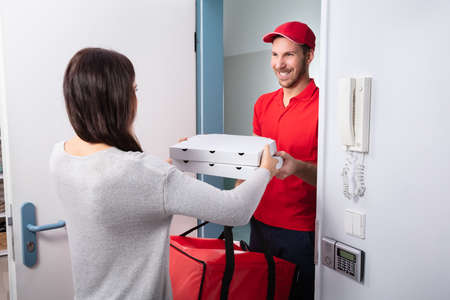 Photo pour Smiling Woman Receiving Pizza From Delivery Man At Home - image libre de droit
