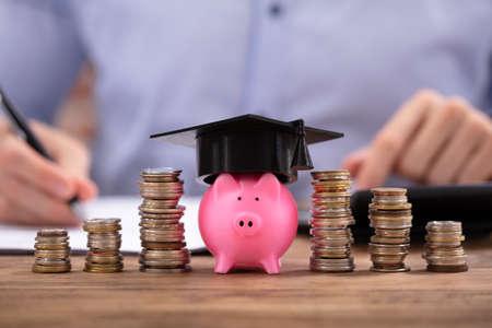 Foto de Stacked Coins And Piggy Bank With Graduation Cap In Front Of Businessman - Imagen libre de derechos