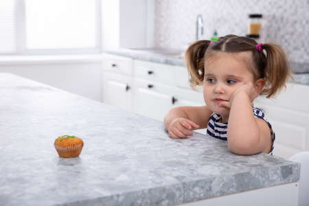 Foto de Close-up Of Girl Looking At Cupcake On Kitchen Worktop - Imagen libre de derechos