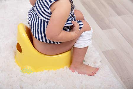 Photo pour Rear View Of Female Toddler Sitting On A Potty Pot - image libre de droit