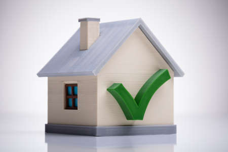 Photo for Miniature House Model With Green Tick Mark On White Desk - Royalty Free Image