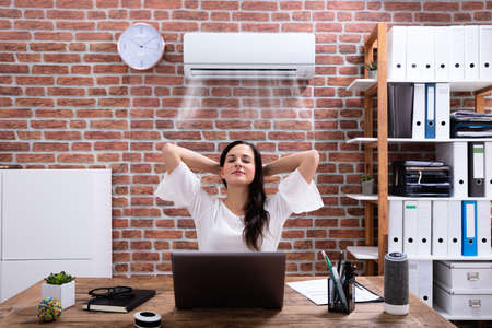 Photo for Relaxed Businesswoman Enjoying The Cooling Of Air Conditioner In The Office - Royalty Free Image