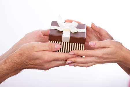 Photo for Close-up Of Couple's Hand Holding Gift Box Against White Background - Royalty Free Image