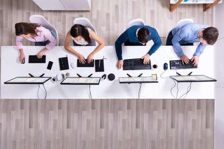 Foto de Young Businesspeople Analyzing Gantt Chart On Computer At Workplace - Imagen libre de derechos
