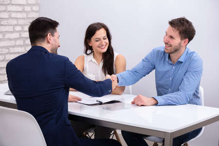 Photo for Close-up Of Advisor Handshaking With A Smiling Young Couple After Deal - Royalty Free Image