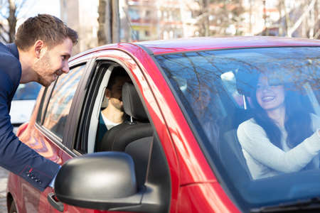 Foto de Smiling Young Man Talking With A Lady Sitting Inside Car - Imagen libre de derechos