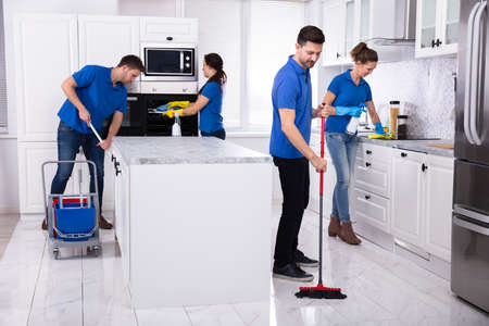 Foto de Group Of Young Janitors In Uniform Cleaning Kitchen At Home - Imagen libre de derechos