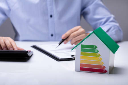 Photo for House With Energy Efficiency Rate In Front Of Businesspeople Working In Office While Using Calculator - Royalty Free Image