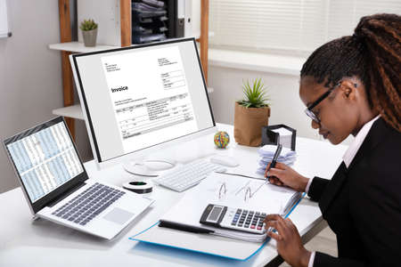 Photo pour Side View Of Young Businesswoman Calculating Invoice On Computer Screen Near Laptop - image libre de droit