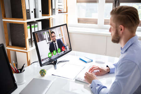 Foto de Side view of businessman video conferencing with coworker on desktop PC at office desk - Imagen libre de derechos