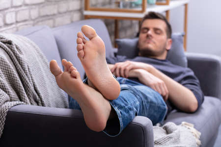 Photo pour Close-up Of Man Relaxing On Sofa With His Legs Crossed In Home - image libre de droit