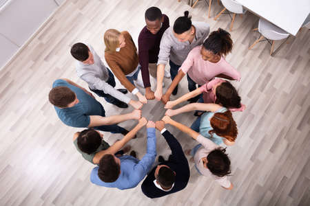 Foto de An Overhead View Of Multi-ethnic People's Hand Joining Their Fist To Form Circle - Imagen libre de derechos