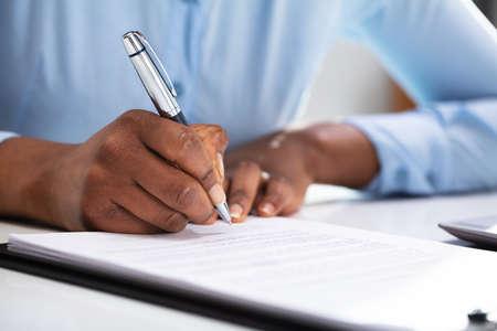 Photo pour Close-up Of A Businesswoman's Hand Filling Contract Form - image libre de droit
