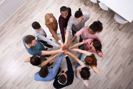 Foto de High Angle View Of Multiracial Friend Stacking Hand Together - Imagen libre de derechos
