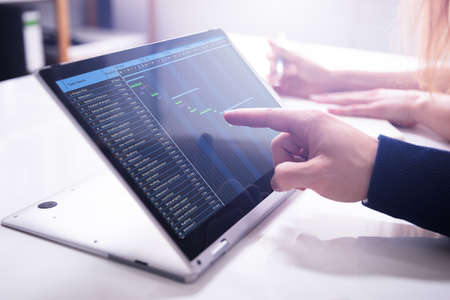 Foto de Close-up Businessman's Hand Showing Gantt Chart On Laptop Screen Over White Desk In Office - Imagen libre de derechos