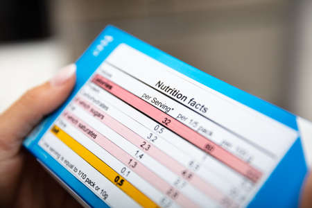 Foto per Close-up Of Woman Reading Nutrition Facts On Box - Immagine Royalty Free