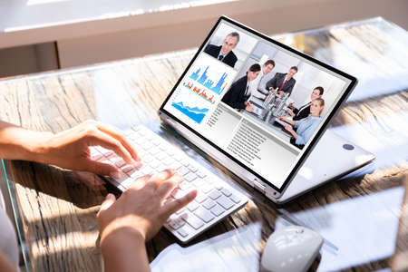 Photo pour Cropped Image Of Businesswoman Using Laptop At Desk For Video Conferencing - image libre de droit
