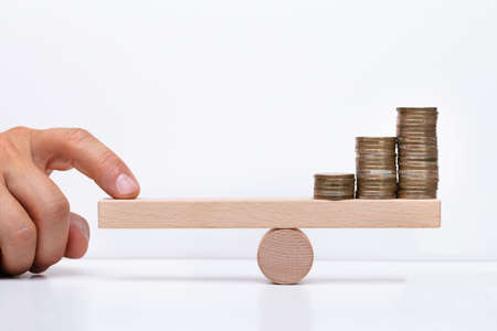 Photo for Close-up Of A Businessperson's Hand Balancing Stacked Coins On Wooden Seesaw With Finger Over Desk - Royalty Free Image