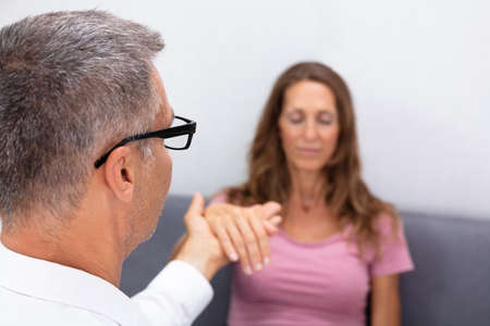 Photo for Close-up Of Professional Hypnotherapist Holding Woman Hand During Hypnotherapy - Royalty Free Image