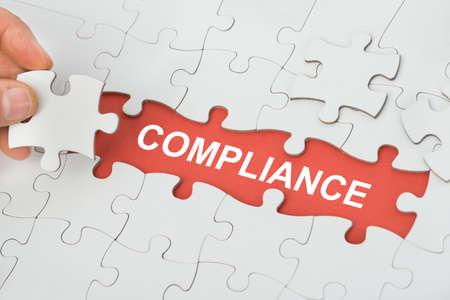 Photo pour Person's Hand Holding Piece Of Puzzle With Word Compliance - image libre de droit