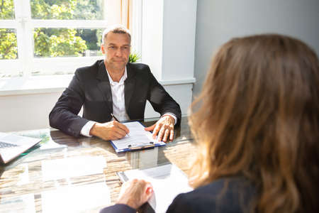 Foto de Mature Businessman Interviewing Female Applicant At Workplace - Imagen libre de derechos