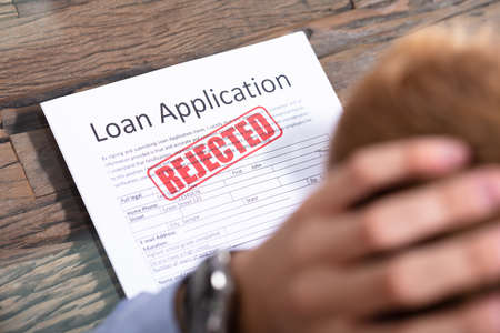 Photo pour Stressed Person Looking At Rejected Loan Application - image libre de droit