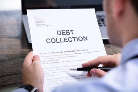 Foto de Man Reading Debt Collection Notice Letter At Desk - Imagen libre de derechos