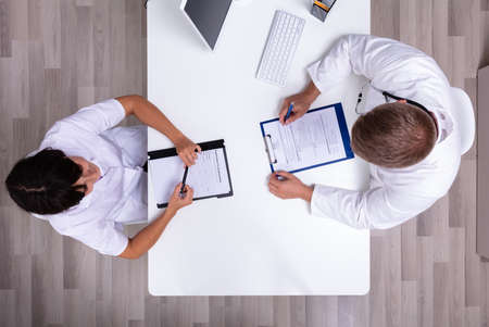 Photo pour Female And Male Doctor Sitting Face To Face Discussing Over A Medical Repor - image libre de droit