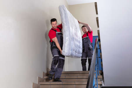 Foto de Two Young Male Movers In Uniform Carrying The Wrapped Mattress While Moving Downward The Staircase - Imagen libre de derechos