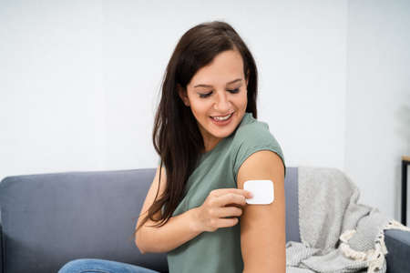 Foto de Woman Applying Patch On Her Arm At Home - Imagen libre de derechos