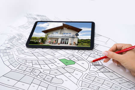 Foto de Hand Holding Pencil Over Cadastre Map New Tablet With House Photo - Imagen libre de derechos