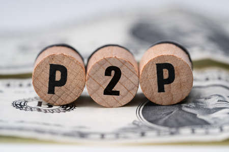 Photo pour Close-up Of A P2p Word On Round Wooden Blocks Over Dollar Bill - image libre de droit