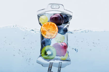 Photo pour Close-up Of Various Fruit Slices In Saline Bag Dip In Water Against White Background - image libre de droit