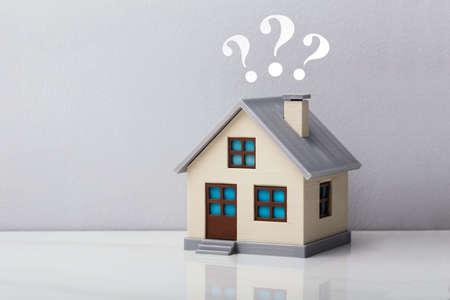 Foto de Small House Model With Question Marks Over Reflective Desk Against Grey Background - Imagen libre de derechos