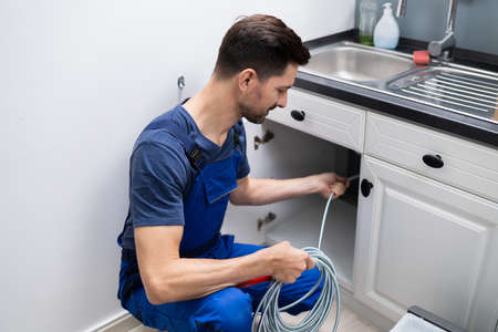 Foto de Male Plumber Cleaning Clogged Sink Pipe In Kitchen - Imagen libre de derechos