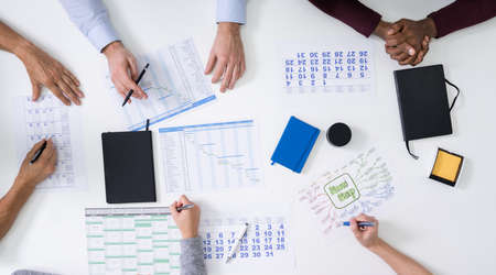 Foto de Group Of People Planning Project Using Gantt Charts And Calendars - Imagen libre de derechos